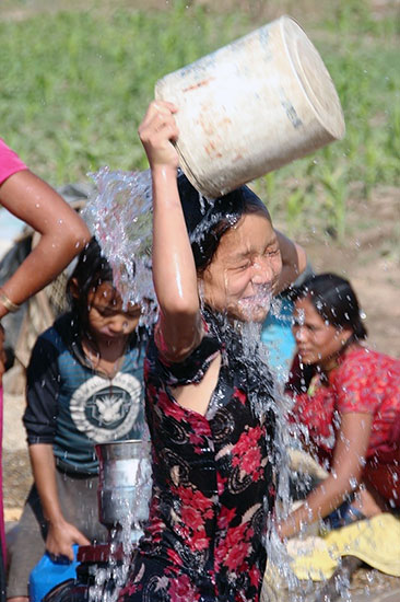 CWON Australia - Clean Water Program - happy Nepalese kid plays in the new water well
